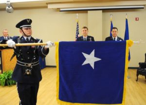 An Air Force Base Honor Guard member unfurls a general officer flag for the first time during a promotion ceremony.